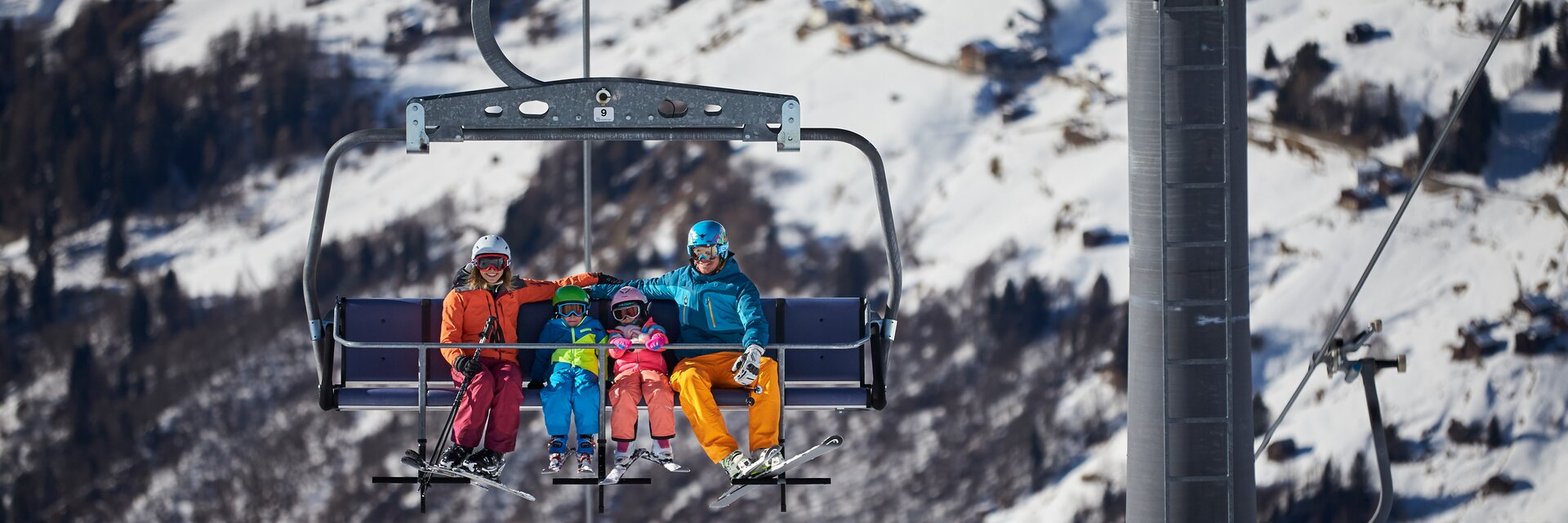 Family happily climbs up the mountain with the chairlift in the ski resort See